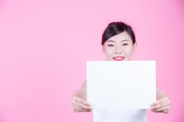 ピンクの背景にホワイトボードシートを保持している美しい女性。 無料写真