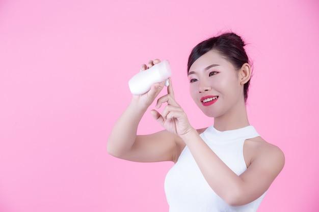 ピンクの背景に製品の瓶を持って美しいアジアの女性。 無料写真