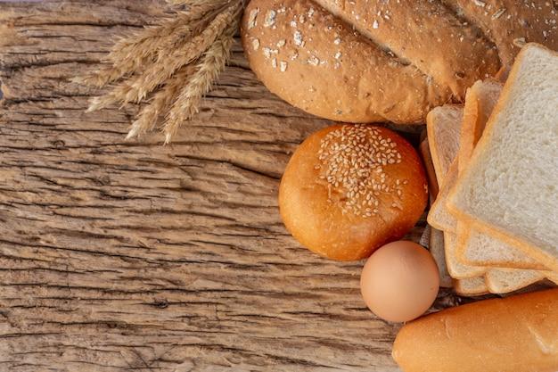 古い木製の背景に木製のテーブルの上のパン各種。 無料写真