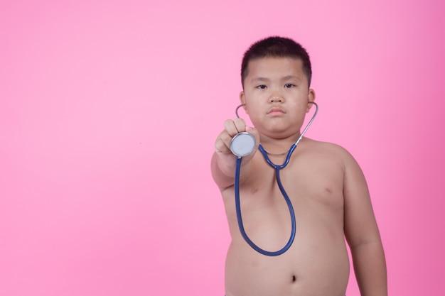 Тучный мальчик, который весит больше нормы на розовом фоне. Бесплатные Фотографии