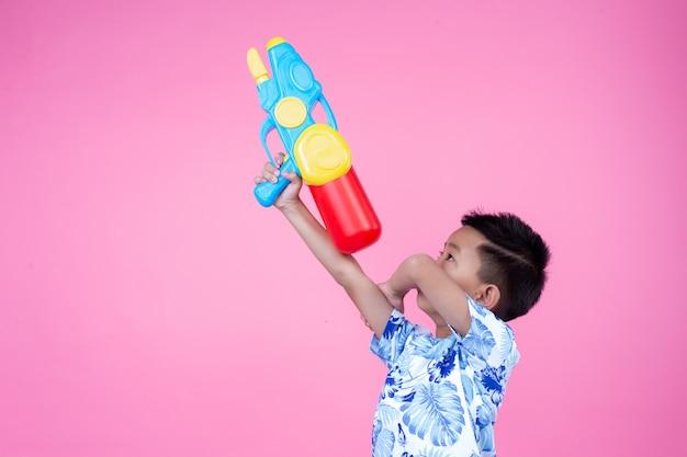 その少年はピンク色の背景に水鉄砲を持っています。 無料写真