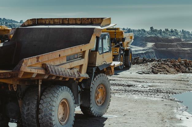 鉱山の後ろと別の前から黄色のトラック Premium写真