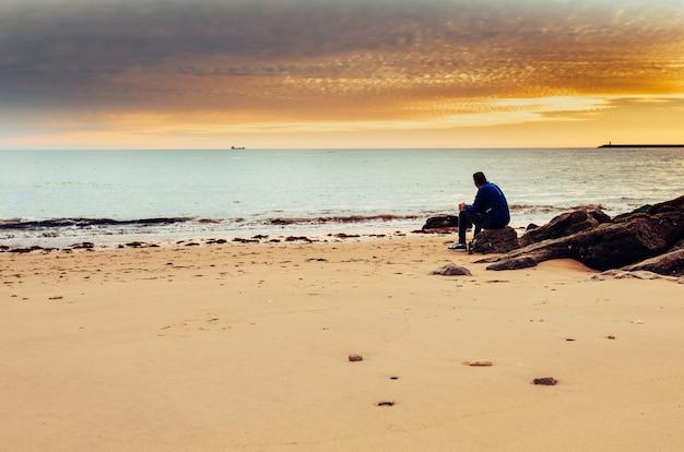 白人男だけで海の岸に座っています。 Premium写真
