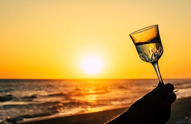 オレンジ色の空と太陽のビーチでワインのロマンチックなガラス Premium写真