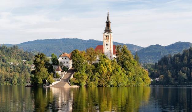 スロベニアのブレッド湖の島にあるマリアの仮定の教会、水に映る Premium写真