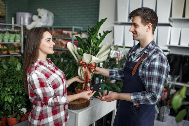 お祝いラッパーで植木鉢を購入することを決定する若い女性の肖像画 Premium写真