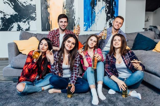 家でビールを飲みながら楽しんで若い陽気な友人のグループ。 Premium写真