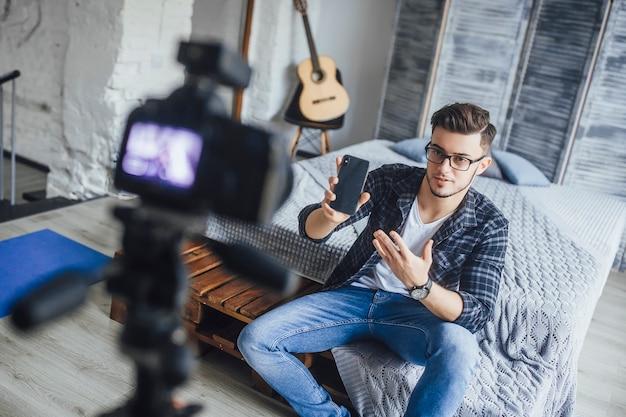 成功したブロガーが自分の部屋で新しい携帯電話について話す Premium写真
