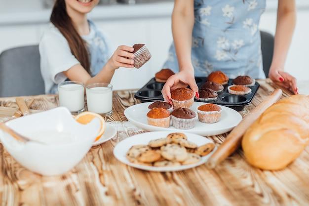 家族がカップケーキとクッキーを一緒に料理する写真 Premium写真