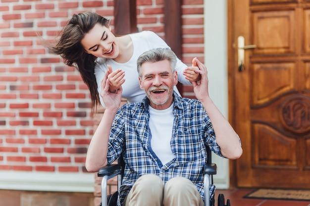 特別養護老人ホーム近くの彼の幸せな孫娘を歓迎する車椅子の陽気な障害の祖父 Premium写真