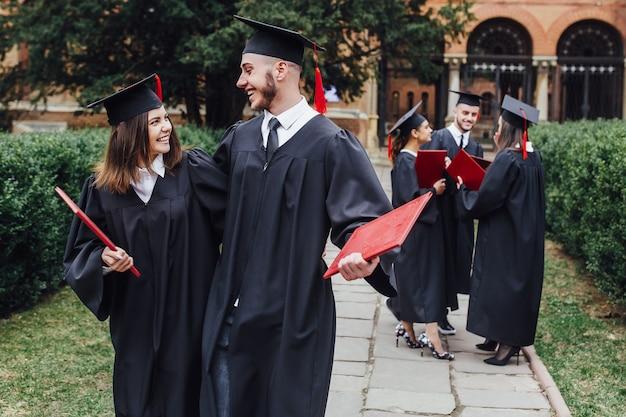大学キャンパスの卒業式ガウンで幸せな学生 Premium写真