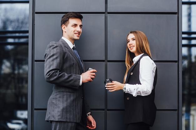 コーヒーを飲みながらビジネスの男性と女性を笑顔の写真は、事務所ビルを破る。ビジネスコーヒータイム。 Premium写真