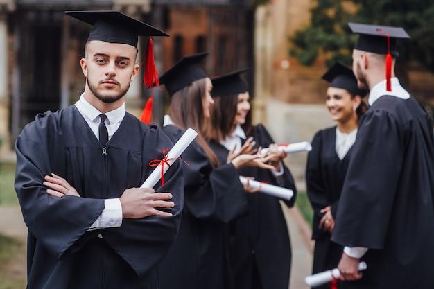 Образование, выпускной и люди. группа счастливых иностранных студентов в классных досках и холостяцких платьях с дипломами Premium Фотографии