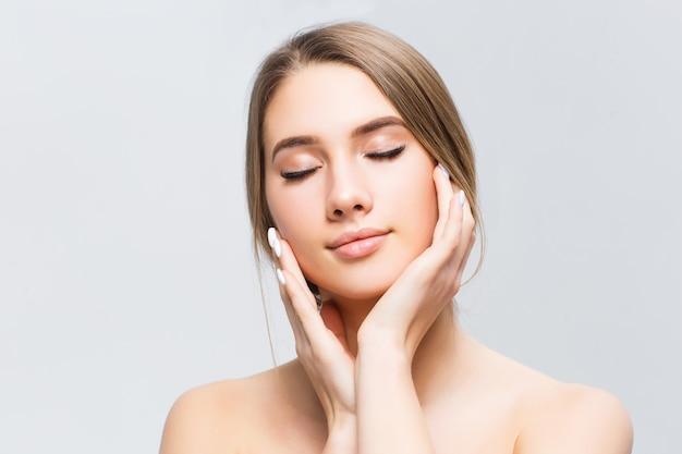 白で隔離され清潔でさわやかな肌を持つ若い成人女性の美しい顔。 Premium写真