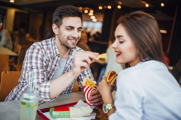 Молодой красивый мальчик кормит свою девушку фаст-фудом. хорошая пара в кафе. Premium Фотографии