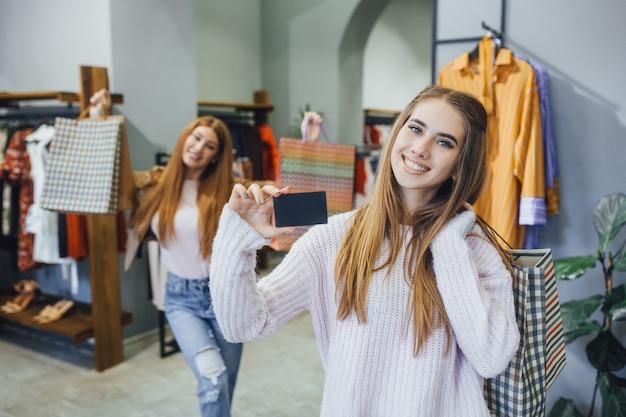 Красивые подруги гуляют в современном торговом центре с помощью кредитной карты Premium Фотографии