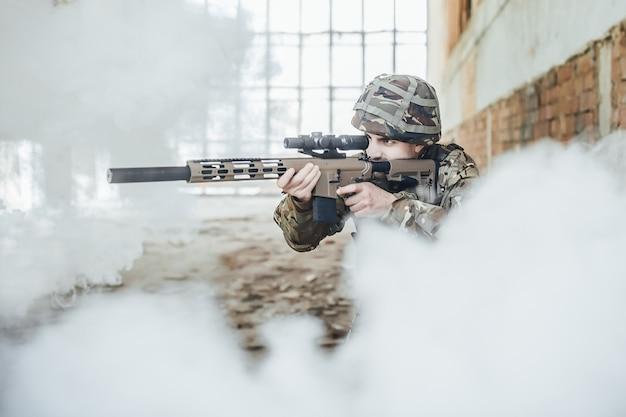 制服を着た軍の兵士は現代のライフルを手に持っており、煙を狙っています Premium写真
