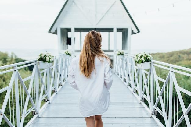 背中の写真。リゾートの早朝のサマーテラス。歩いている白いシャツの女性。 Premium写真