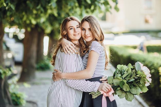 若い美しいブロンドの娘は、街の通りで彼女の中年のお母さんを抱擁します。彼らは幸せで、お互いを愛しています。 Premium写真
