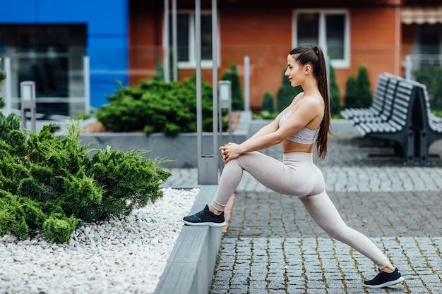 ストリート、アウトドアスポーツ、フィットネススタイルでヨガフィットネス運動を行うファッションスポーツウェアのフィットネススポーツ少女。 Premium写真
