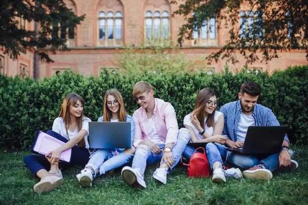 キャンパスに座ってラップトップを探している学生のグループ。 Premium写真
