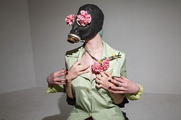 防毒マスクとマントを着て、ピンクのプラスチックの花を保持している緑の髪の面白い女の子。誰かが彼女を後ろから持っている手。クレイジー遊び心のあるハメ撮りコンセプト Premium写真