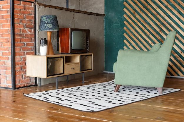 カーペット、昔ながらのアームチェア、レトロなテレビ付きのビンテージルーム Premium写真