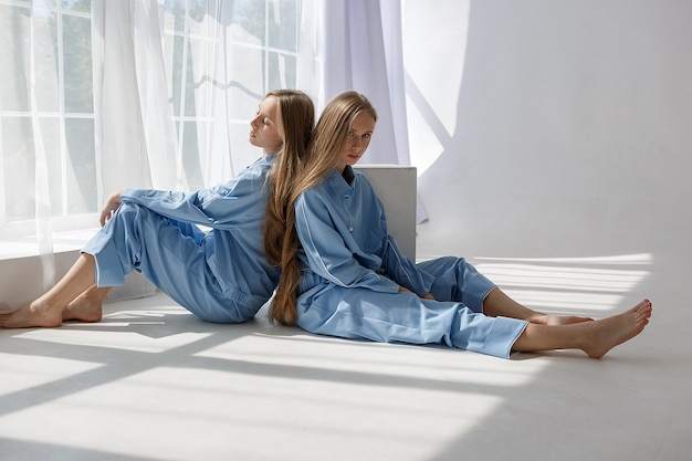 Две молодые девушки-близнецы в одинаковых синих костюмах сидят на полу с белым циклорамой Premium Фотографии