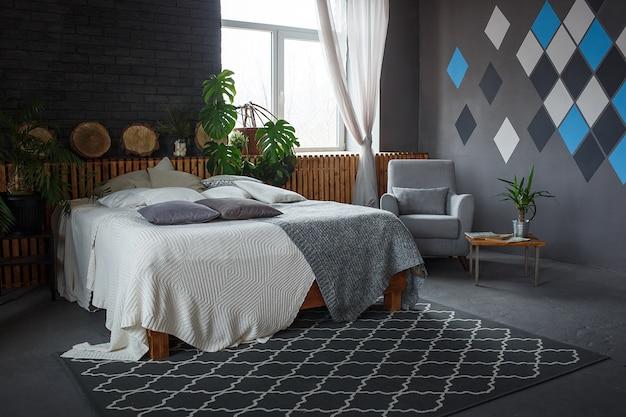 Стильный лофт уютная гостиная с двуспальной кроватью, креслом Premium Фотографии