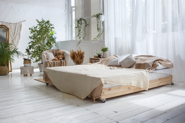 スタイリッシュなロフトの居心地の良いベッドルーム、ダブルベッド、肘掛け椅子 Premium写真