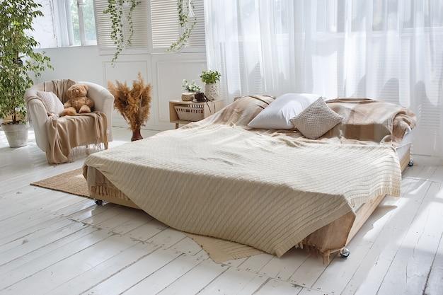 Стильная лофт уютная спальня с двуспальной кроватью, креслом Premium Фотографии