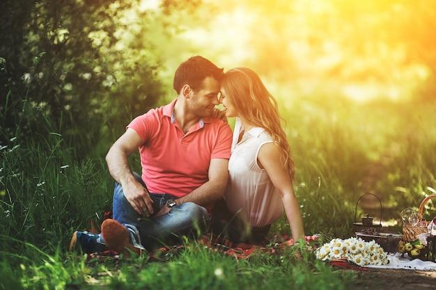 夫婦はお互いの目を見て、草の上に座って 無料写真