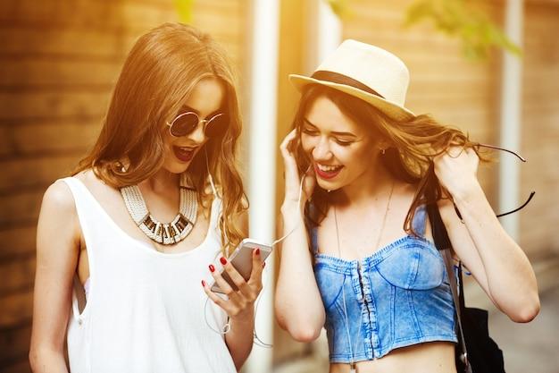 日没時の携帯電話の画面を見て幸せな友人 無料写真