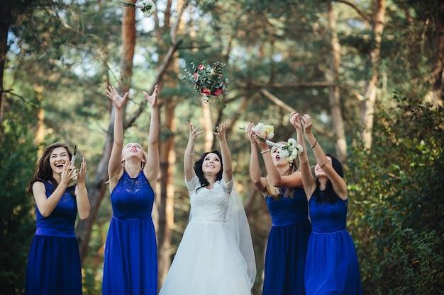 ブーケを投げる花嫁と花嫁介添人 無料写真