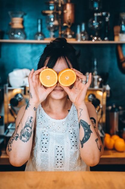 笑顔で目の前でオレンジを保持している肖像成人女性。 無料写真