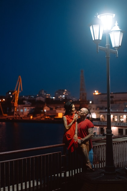 Парень и девушка обнимали друг друга на фоне ночного порта Бесплатные Фотографии