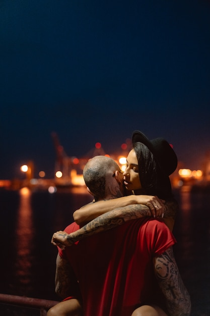 夜の港の背景にお互いを抱いて男と女 無料写真
