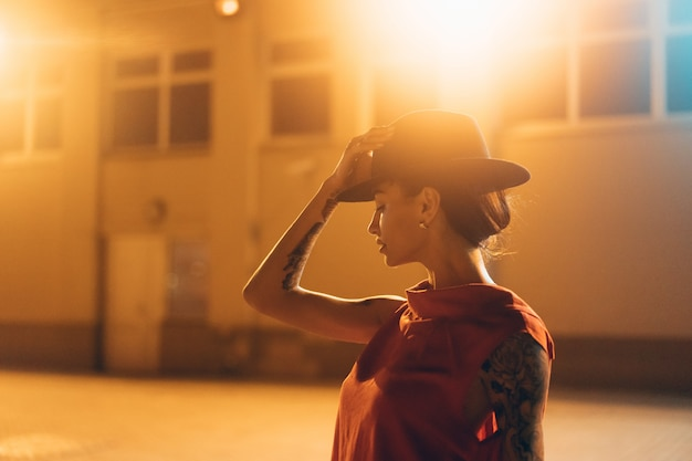 帽子の若い、魅力的な女の子が夜にカメラにポーズします。 無料写真