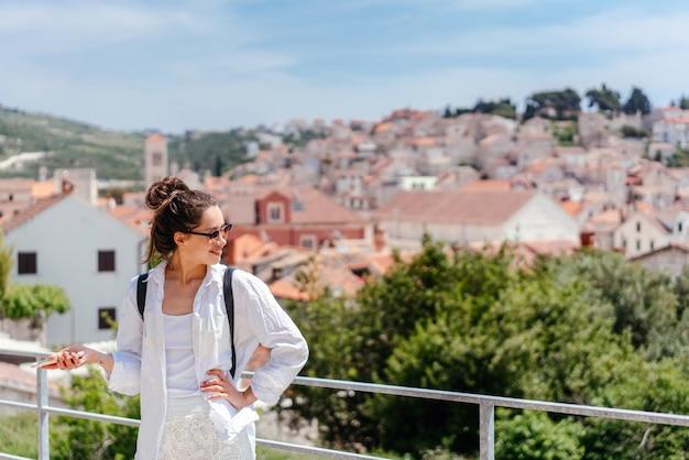 クロアチアの小さな町を見下ろすバルコニーの若い美しい女性 無料写真