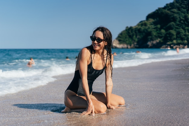 海で彼女の膝の上でポーズセクシーな若いブルネット 無料写真