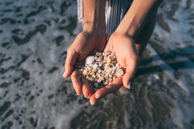 女性の手は小さな小石をたくさん持っています 無料写真