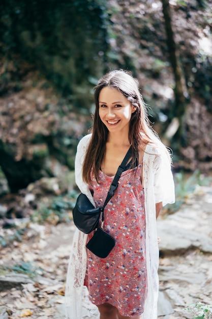 魅力的な女性は、カメラでポーズをとって公園を歩いています。 無料写真