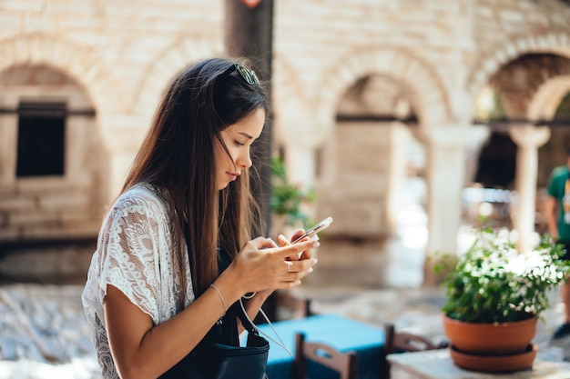 電話で魅力的な女性が立っています。女の子はメッセージを入力しています。 無料写真