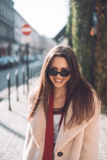 ピンクのコートを歩いて若い美しいスタイリッシュな女性 無料写真