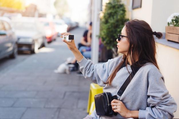 カメラでポーズかわいい、若い女性のブロガー。 無料写真