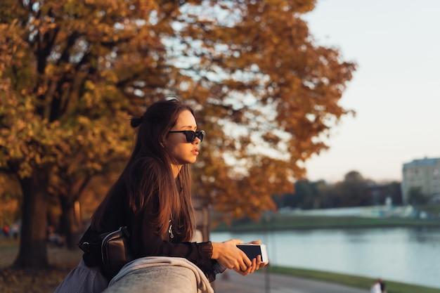 Привлекательная женщина, используя смартфон на открытом воздухе в парке Бесплатные Фотографии
