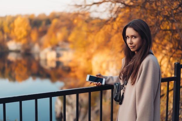 秋の公園に立っている美しいエレガントな女性 無料写真