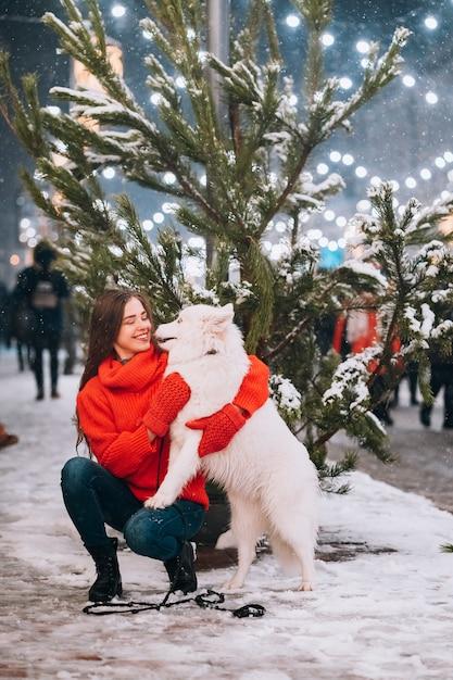 女性が夜の街で犬を抱いています。 無料写真