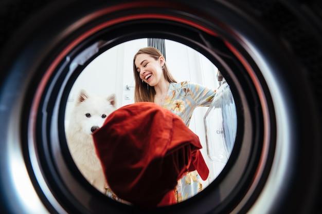 自宅の若い女性は、乾燥機にドレスを置きます。 無料写真