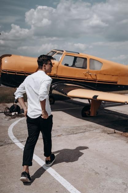 小さな単一のエンジン飛行機の背景に立っている男。 無料写真